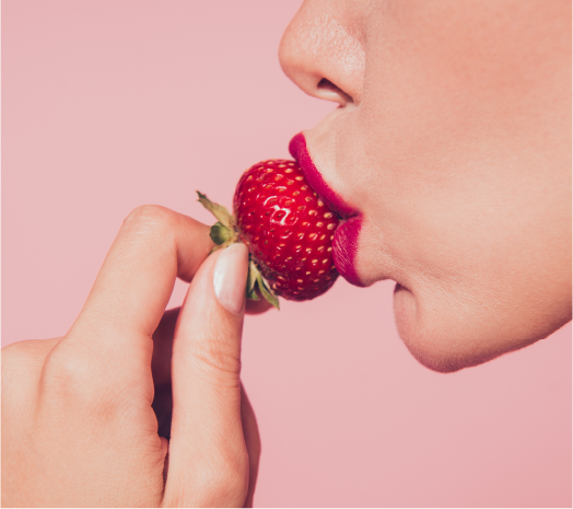 A person kissing a strawberry